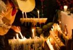 Niño en traje tradicional prendiendo velas en Festival de vida y muerte de Xcaret.